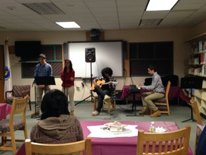 Students playing the guitar and singing in the library during Literary Arts Night