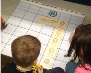 Two students bend over a chart with squares drawn on it. There are yellow cards with directional arrows laid out on the grid and one student holds a Bee Bot robot in their hands. They are attempting to direct the robot to the target.