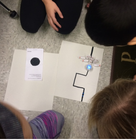 Four students surround a piece of paper with a black path drawn on it. They are attempting to program the Ozobot robot to knock down some bowling pins.