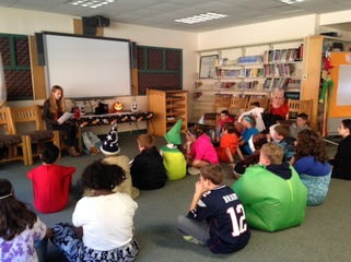 A high school student reads a story to middle school students who are dressed up in costumes.