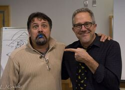 Photograph of illustrator Ralph Masiello wearing a tan sweater with a piece of blue tape in his mouth. David is pointing at him. They are both smiling.