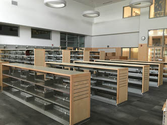 Rows of empty bookcases sit in the new library space. There are low cases and higher cases.