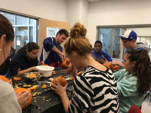 A group of students sits at tables carving pumpkins