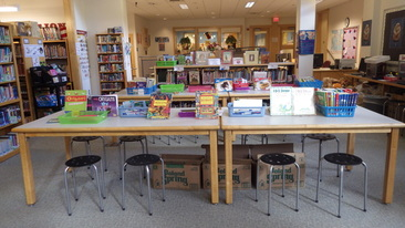 Table featuring a variety of art-themed books and materials.
