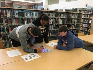 Three students (one female and two males) are clustered around a worksheet on a table. They are using a UV pen to try and solve the puzzle.