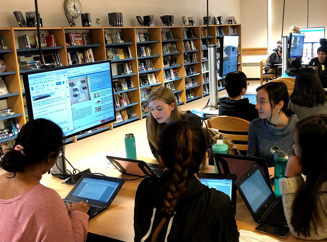Five high school female students are seated around a wooden table with their Chromebooks and looking at a large computer screen that is raised at the end of the table, so all of them can see it while working.